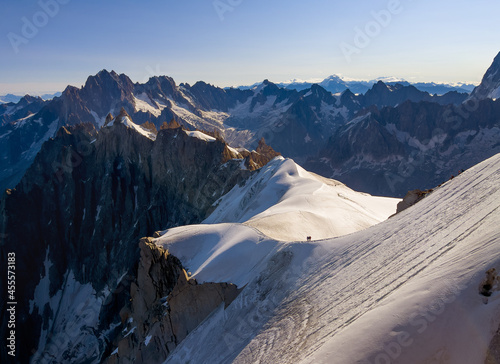 French Alps mountains peaks panorama view with silhouettes of climbers as roping team descending on the snowy slope under Aiguille du Midi 3842m Fototapet