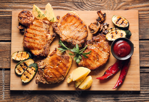Board with tasty pork steaks, tomato sauce and grilled vegetables on wooden background