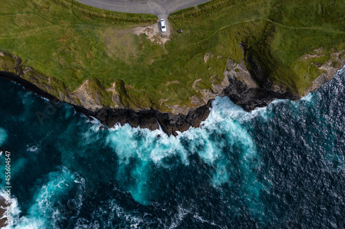 Obraz na plátně Birds eye view of car parked at end street of the famous Moher Cliff in Ireland