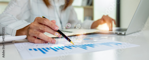 Stampa su Tela Close up of Business woman accountant or financial expert coins double exposure analyze business report graph finance chart corporate finance economy banking business stock market research concept