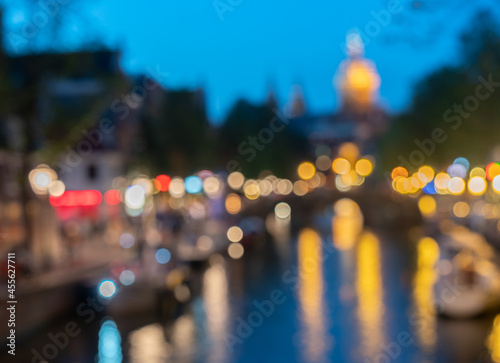 Amsterdam urban night and travel abstract backgrounds defocused lights and buildings along canal with Saint Nicholas Basilica church tower against blue sky Fotobehang