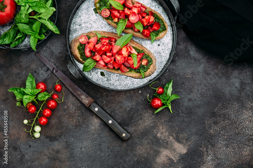 Fotografie, Obraz Bruschetta with pesto and tomatoes on a dark background
