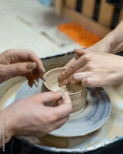 a ceramic artist teaches a student the technique of modeling on a potter's wheel Fototapet