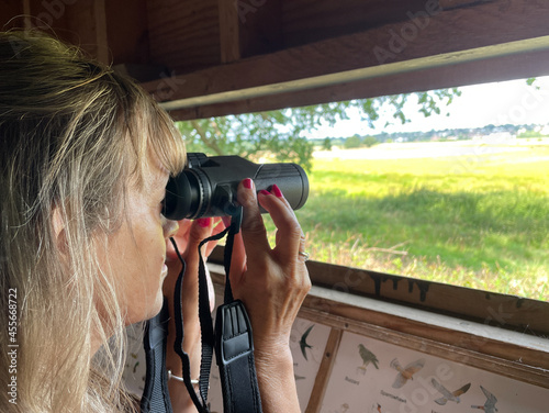 Stampa su Tela Lady looks with binoculars out of a bird hide with countryside in background