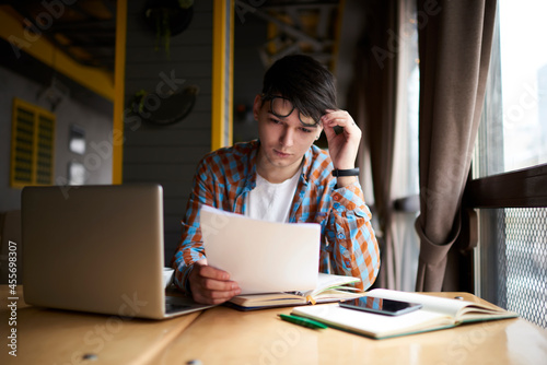 Fotografie, Obraz Young millennial male sitting at table front open laptop computer while studying online