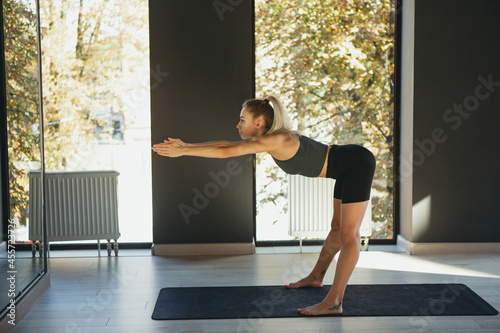 Fototapeta Beautiful young slim sportive woman in sportswear doing yoga exercise on gray mat at yoga sport center