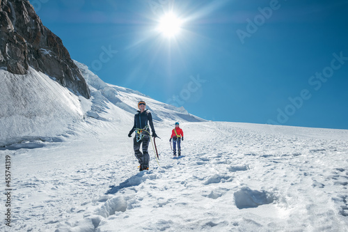 Fotografering Two laughing young women Rope team descending Mont blanc du Tacul summit 4248m dressed mountaineering clothes with ice axes walking by snowy slopes