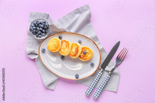 Plate with cottage cheese pancakes and blueberry on color background