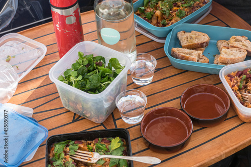 Fototapeta A picnic dinner on a motorboat during summer with salad and rice and beans