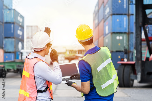 Fotografering Foreman manual worker at commercial dock, wearing yellow, white safety helmet, h