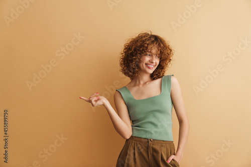 Slika na platnu Young ginger woman laughing and pointing finger aside