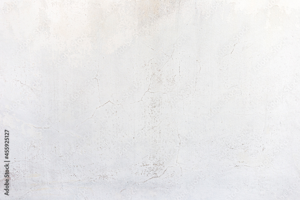 Old white cement wall background with cracks.
