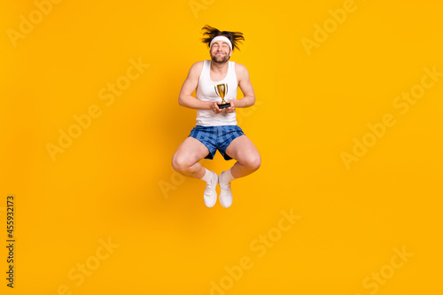 Fotografie, Tablou Full length body size view of attractive cheerful dreamy guy jumping getting cup