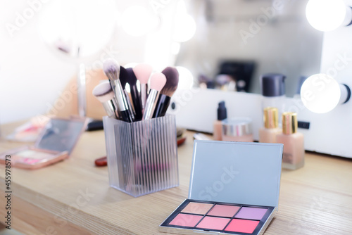 Fotografering Close-up Powder set without foundation or pressed powder color gradation in square, makeup brushes and skin creams, on the dressing table with a mirror
