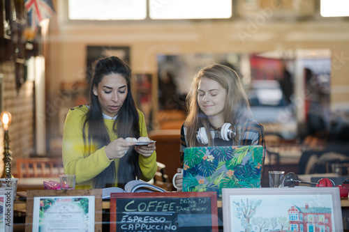 Young female college students studying, eating dessert at cafe window