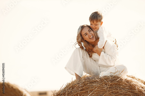 Mom and son are sitting on a haystack in the field at sunset Fototapet