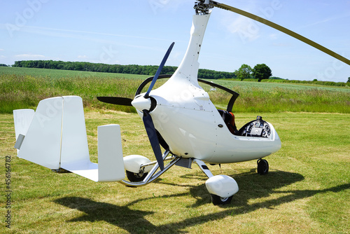 Murais de parede White gyrocopter rear side view canopy open parked on grass runway