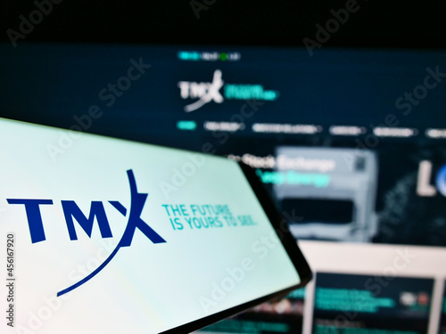 Fototapeta premium STUTTGART, GERMANY - Mar 07, 2021: Smartphone with logo of financial services company TMX Group Limited on screen in front of website.