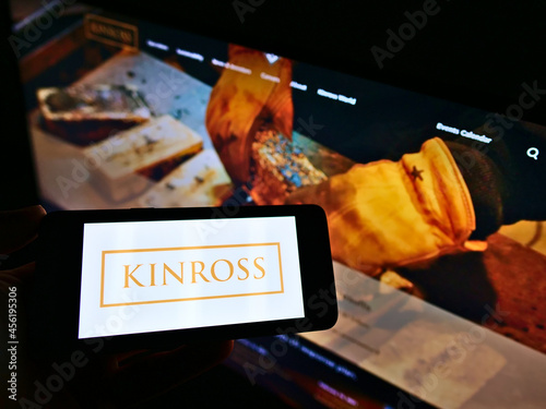 Fototapeta premium STUTTGART, GERMANY - Mar 05, 2021: Person holding mobile phone with logo of Kinross Gold Corporation on screen in front of web page.