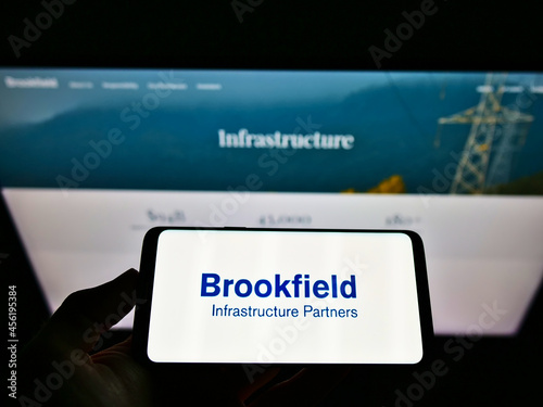 Fototapeta premium STUTTGART, GERMANY - Mar 05, 2021: Person holding cellphone with logo of Brookfield Infrastructure Partners LP on screen with web page.