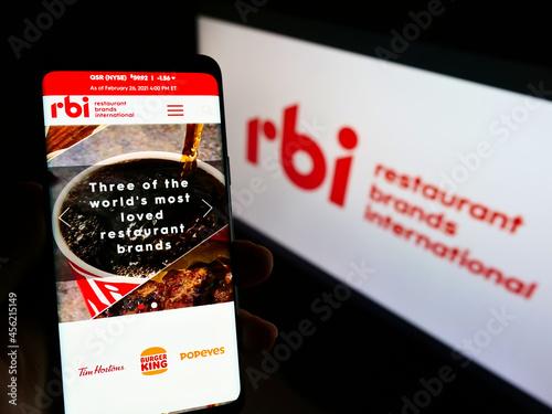 Fototapeta premium STUTTGART, GERMANY - Mar 03, 2021: Person holding mobile phone with web page of Restaurant Brands International (RBI) on screen.