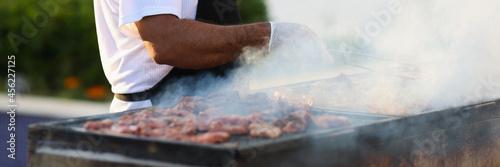 Obraz na płótnie Cook prepares meat on grill on street