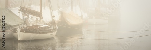 Fotografie, Obraz Elegant and modern yachts, sailing and fishing boats, small ships moored ti a pier in a thick fog