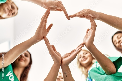 Foto Group of young volunteers woman smiling happy make heart symbol with hands together at charity center