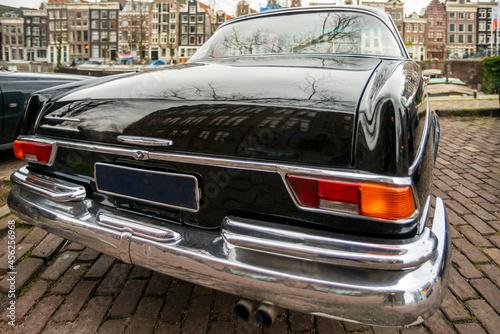 Fotografie, Obraz Rear of a black vintage vehicle parked on a cobblestone sidewalk
