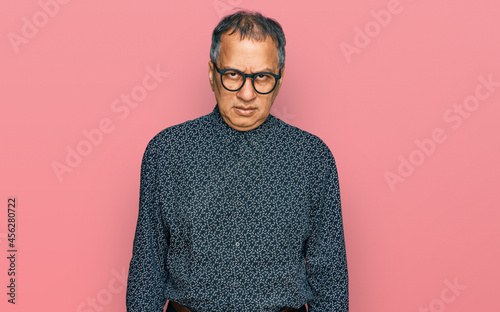 Obraz na plátně Middle age indian man wearing casual clothes and glasses skeptic and nervous, frowning upset because of problem