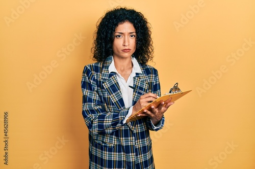 Fototapeta Young latin girl wearing business clothes writing on clipboard skeptic and nervous, frowning upset because of problem