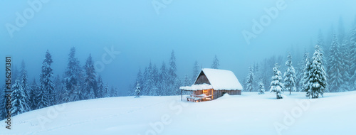 Fotografiet Fantastic winter landscape panorama with glowing wooden cabin in snowy forest