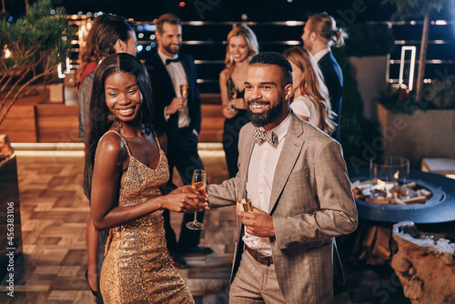 Fotografiet Beautiful young African couple in formalwear holding champagne flutes and smilin