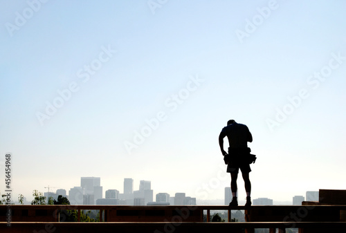 Fotografiet Carpenter standing on the top of a wood framed wall with a view of the city