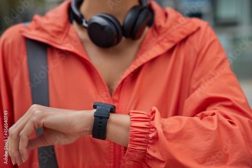 Fototapeta premium Unrecognizable woman checks fitness activity on smartwatch trains outdoors checks pulse and results after cardio workout uses headphones for listening music from playlist. Modern sport gadgets