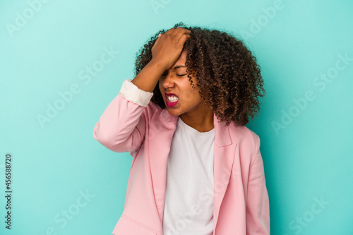 Fotografiet Young african american woman with curly hair isolated on blue background forgetting something, slapping forehead with palm and closing eyes