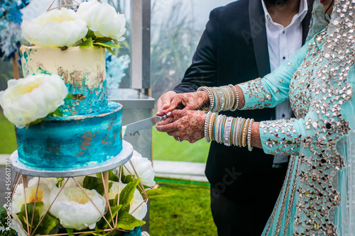 Canvas Indian couple's cutting a wedding cake hands and knife close up