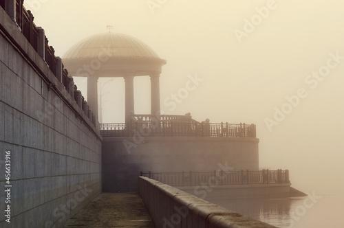 Fotografiet Sunrise time on a foggy embankment overlooking the rotunda