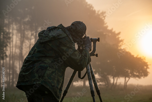 Fotografia Nature photographer standing in camouflage clothing with a camera on a tripod