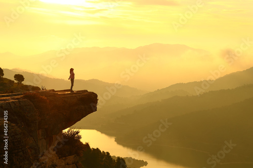 Canvas Woman breathing in the top of a cliff at sunrise in the mountain