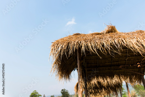 Fotografiet A wooden hut with a roof made of cane grass.