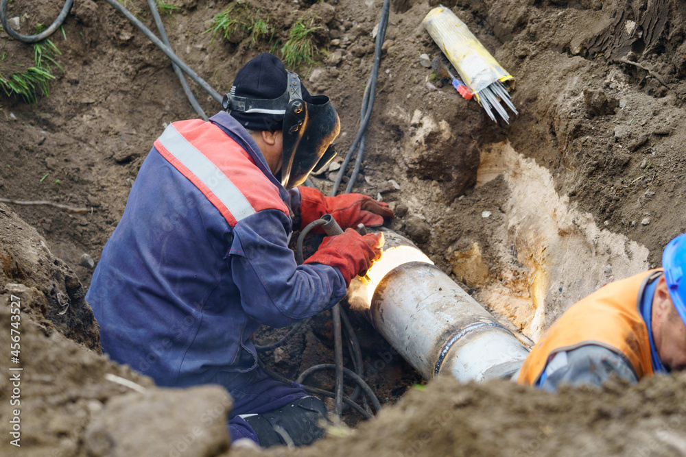 Plumber standing in pit is engaged in elimination of communal accident outdoors. Utility worker fixing broken water main. Welding work to replace rotten elements of water pipe. Sewerage pipe repair