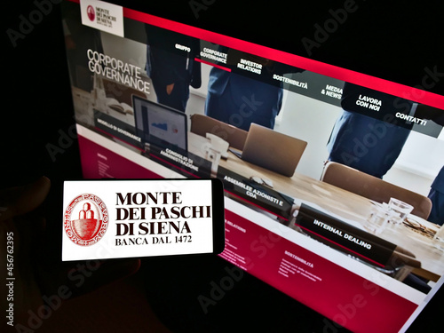 Fototapeta premium STUTTGART, GERMANY - Feb 11, 2021: Person holding cellphone with logo of Banca Monte dei Paschi di Siena (BMPS) on screen with web page