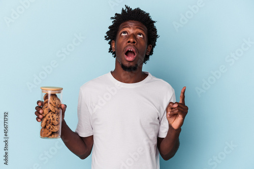 Obraz na plátně Young african american man holding chocolate chips cookies isolated on blue background pointing upside with opened mouth