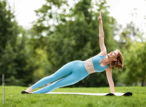 Fototapeta premium Happy smiling young woman in sportswear standing in Side Plank Vasisthasana pose outside in nature