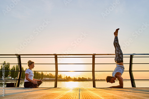 Couple practicing acrobatic yoga together, doing Handstand pose on nature outdoors at sea Fototapet