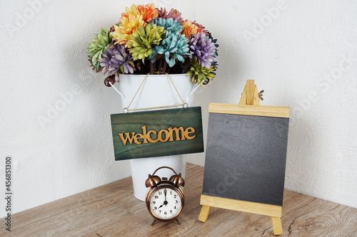 Vászonkép Wooden easel with welcome board and daisy flower bouquet
