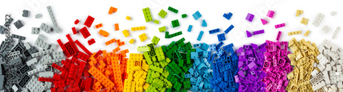 Foto top view of wide pile various colorful rainbow colored stackable plastic toy bricks isolated white panorama background