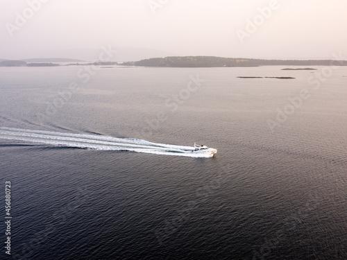 Obraz na plátně Boat speeding over fjord water