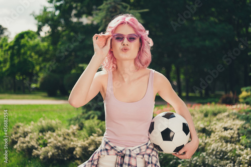 Fototapeta premium Photo of young sporty girl happy positive smile pouted lips send air kiss flirty hold football play outdoors